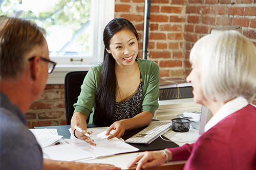 Young credit counsellor woman talking to a mature couple during a meeting in the office