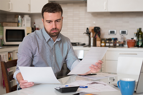 Worried middle aged guy looking at bills and a computer in the kitchen