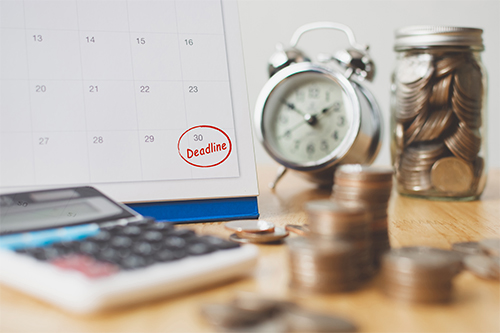 Close up of a table with coins, calculator and calendar showing a red deadline for the end of the month