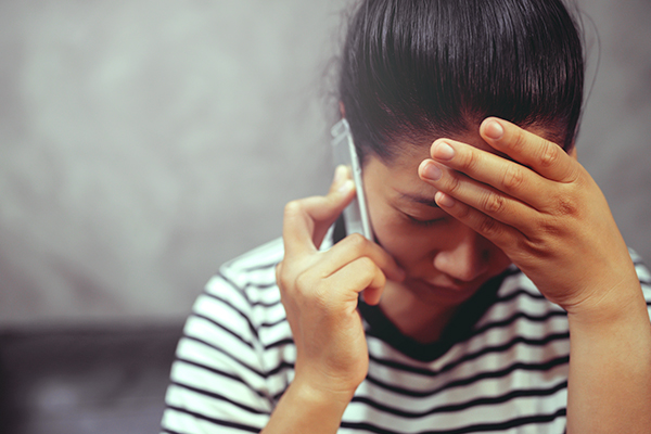 Anxious brunette woman having frustrated stressed expression, holding one hand on her head and a phone with her other one