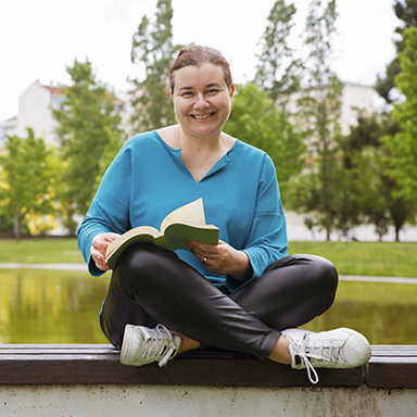 Woman smiling at the camera while holding a book