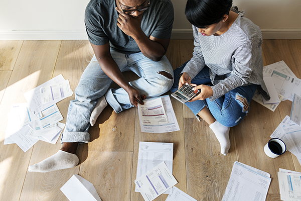 Couple sitting on the floor with a calculator, with a lot of bills around them