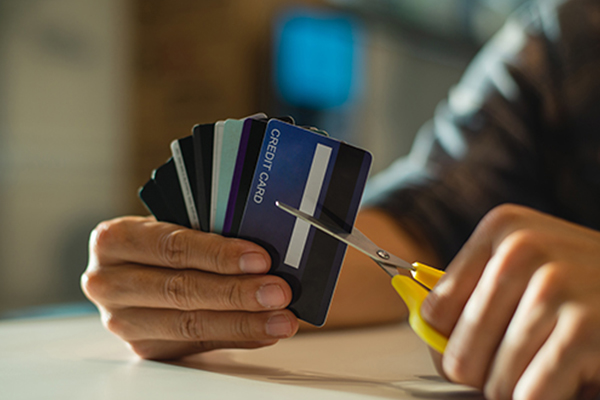 A person cuts up their credit cards