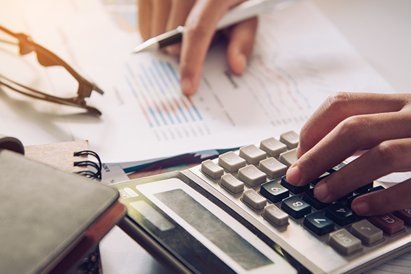 Businessman's hands with calculator and checking the financial data
