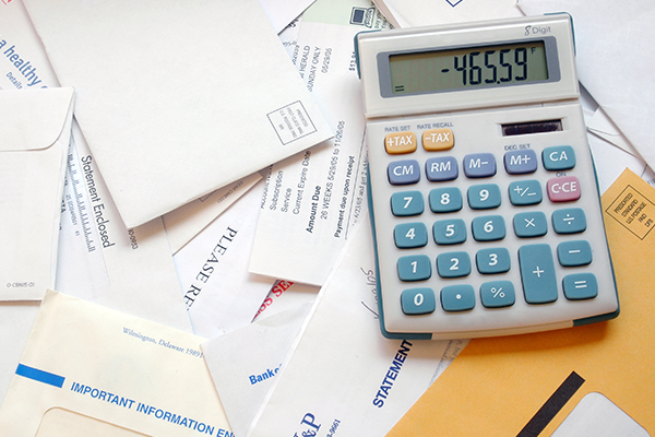 Close up of a table full of letters and bills, with a calculator on it