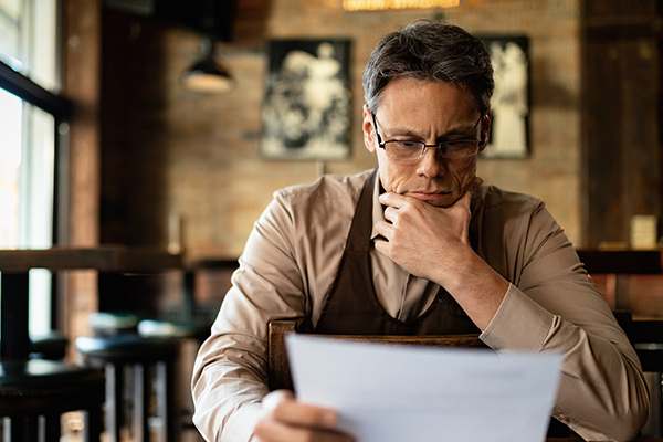 A man reviews his small businesses' financial statements