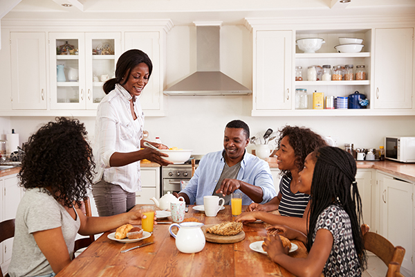 Family of five people eating breakfast at kitchen table