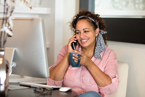 A woman drinks coffee and discusses an orderly payment of debt program over the phone.