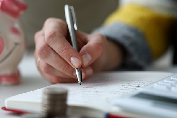 A person writing their budget in a notebook.