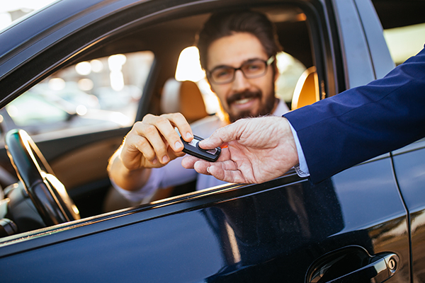 A man in the front seat of a car accepts the keys to his new car.