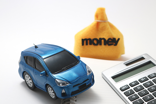 Blue plastic toy car next to a yellow bag with money written on it and a calculator