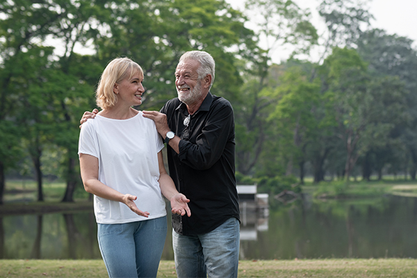 Happy mature couple walking in a park while holding each other