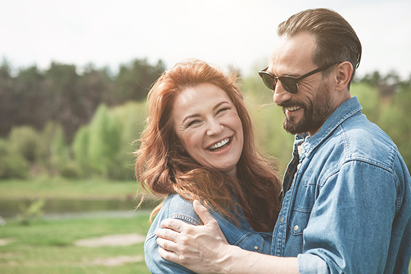 Young couple embracing, smiling at camera