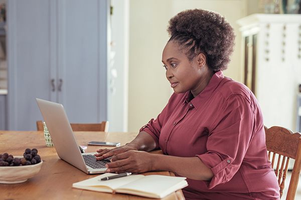 A woman resarches the long term consequences of insolvency option on her laptop.