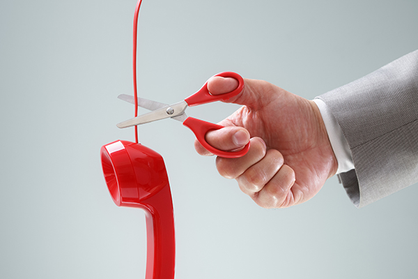 Person cutting telephone cord with scissors