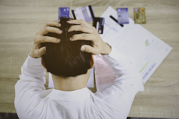 Man holding his head looking at multiple credit cards on the table