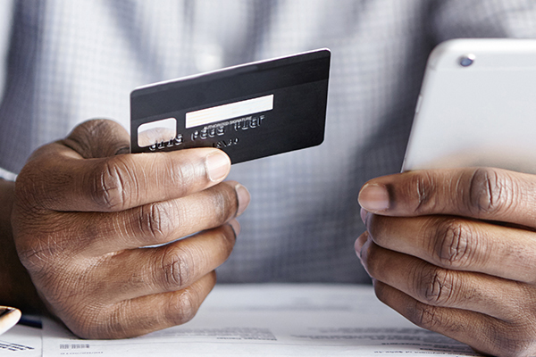 Close up man hand holding credit card and mobile phone sitting at a table